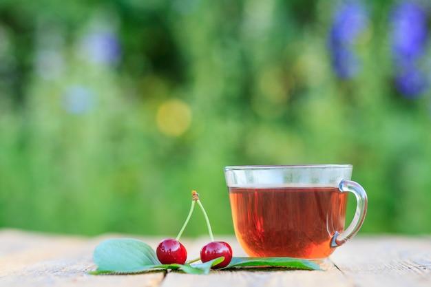 ぼやけた自然な背景の古い木の板に花柄とお茶と赤い熟した桜の果実のガラスカップ