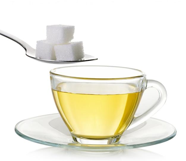 お茶と分離された砂糖のガラスのコップ