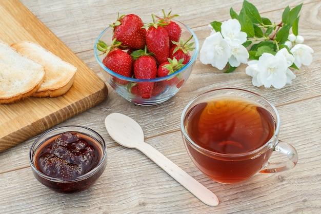 차 한 잔, 수제 딸기 잼, 나무 커팅 보드에 있는 빵, 나무 배경에 신선한 딸기, 숟가락, 흰색 자스민 꽃. 평면도.