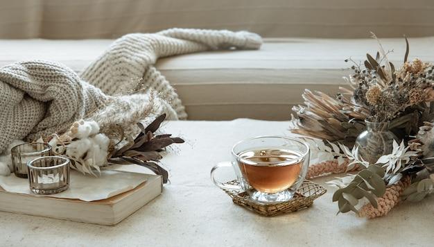 部屋のインテリアにお茶、ニット要素、ドライフラワーのガラスのカップ。