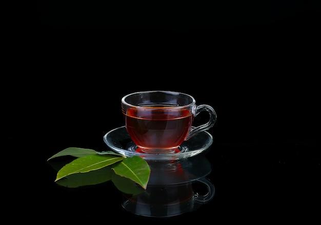 Стеклянная чашка чая на черном