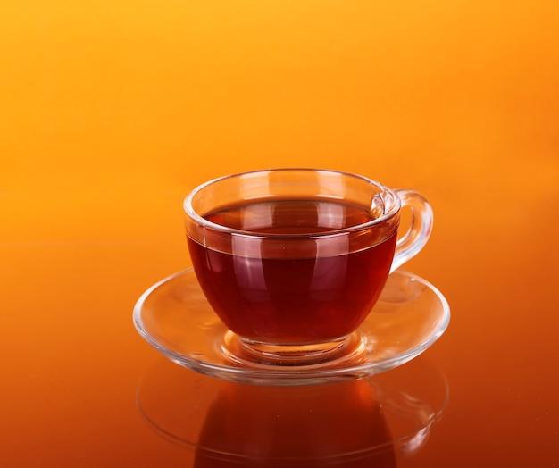 Стеклянная чашка чая на апельсине