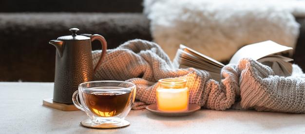 Стеклянная чашка чая, чайник, свеча и книга с вязанным элементом. понятие домашнего уюта и тепла.