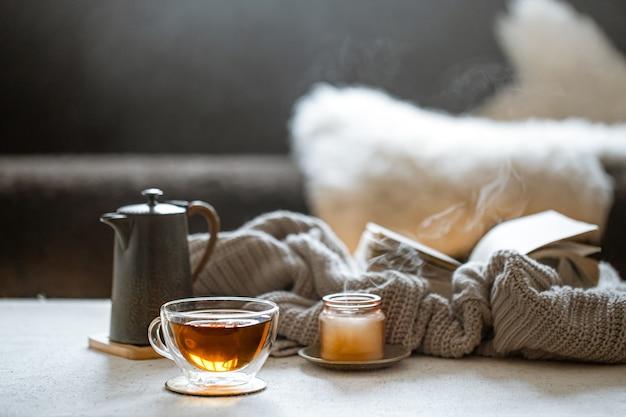 Стеклянная чашка чая, чайник, свеча с вязанным элементом. понятие домашнего уюта и тепла.