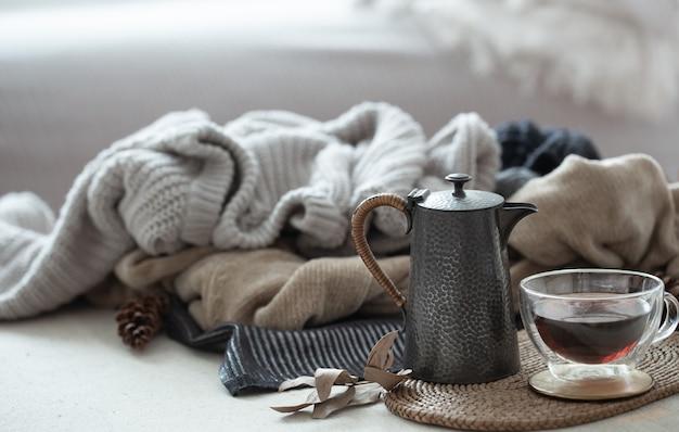 Стеклянная чашка чая с чайником на фоне теплой одежды в холодных тонах.
