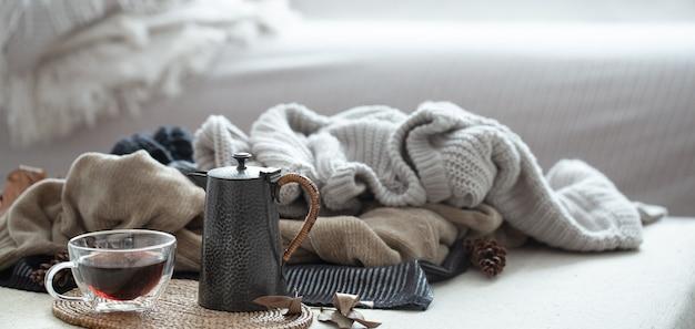 Стеклянная чашка чая с заварником теплая одежда в холодных тонах. осенняя композиция горизонтальная