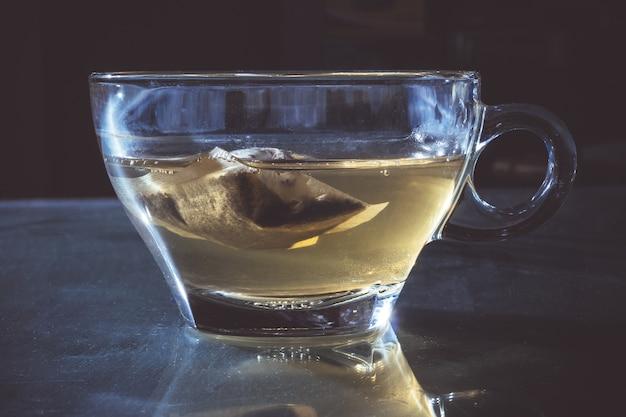 暗い背景にバッグと紅茶のガラスのカップ