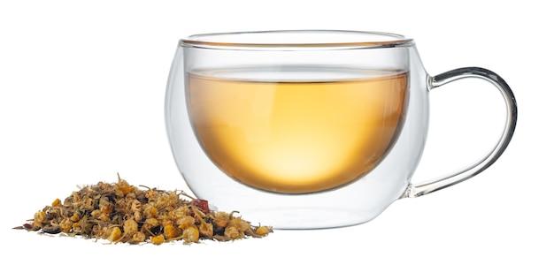 白い背景で隔離の乾燥茶葉とお茶のガラスカップ