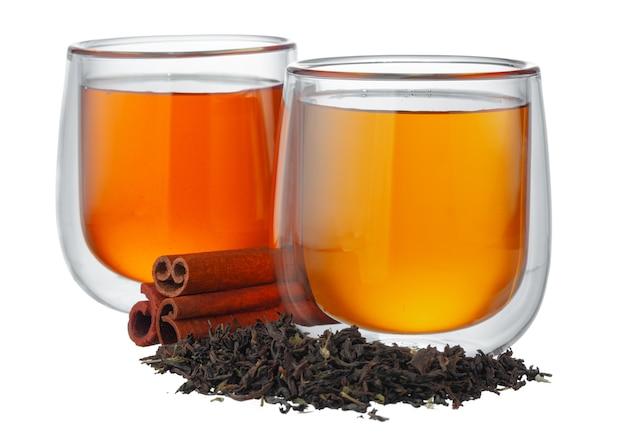 白で隔離乾燥茶葉とお茶のガラスカップ