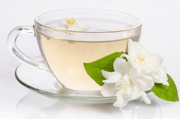 Стеклянная чашка чая с жасминовыми цветами и листьями