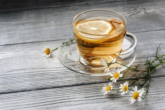 木製の背景にレモンとカモミールの花とお茶のグラス。