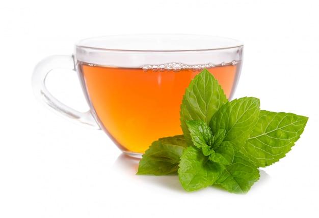 ホワイトスペースで分離されたミントの葉とお茶のガラスのコップ