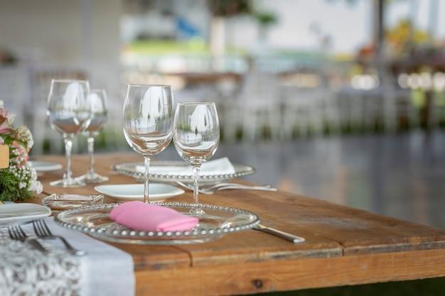 멕시코의 사교 행사를 위해 정원에 꽃꽂이가 있는 테이블 위의 유리 컵