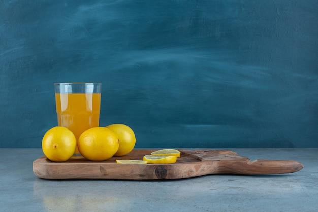 Una tazza di vetro di succo d'arancia con limoni freschi.