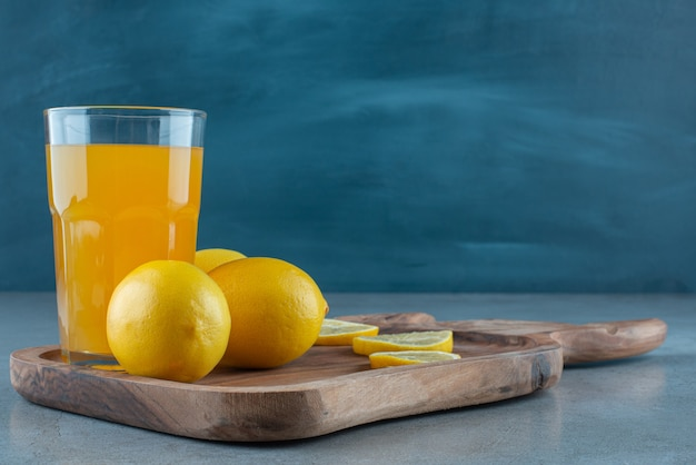 A glass cup of orange juice with fresh lemons .