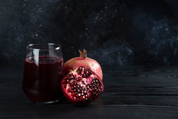 A glass cup of pomegranate juice on dark.
