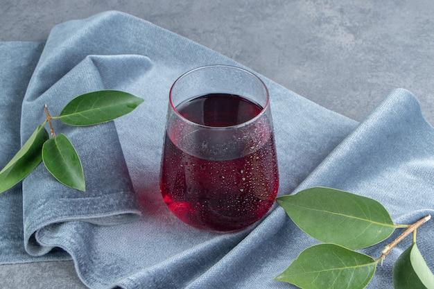 Una tazza di vetro di succo di melograno con cubetti di ghiaccio su una tovaglia
