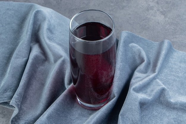 A glass cup of pomegranate juice with ice cubes on a tablecloth