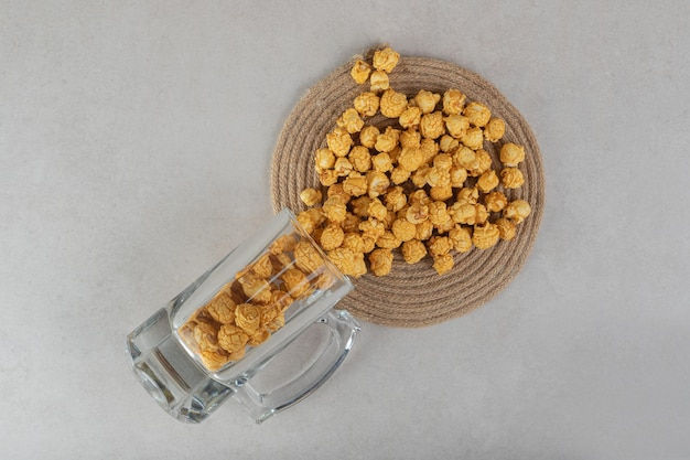 Glass cup of popcorn candy spilling over a trivet on marble surface.