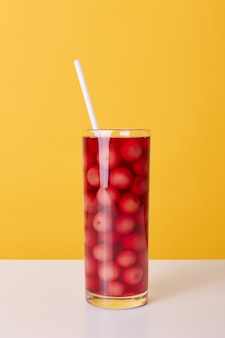 Glass cup of red cocktail with drinking tube and cherries isolated over yellow background, fresh non alcoholic summer beverage on table.