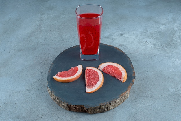 A glass cup of red juice with slices of grapefruit .