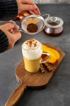 A glass cup of spicy pumpkin cappuccino on grey surface