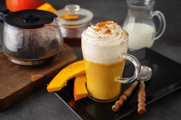 A glass cup of spicy pumpkin latte on dark surface