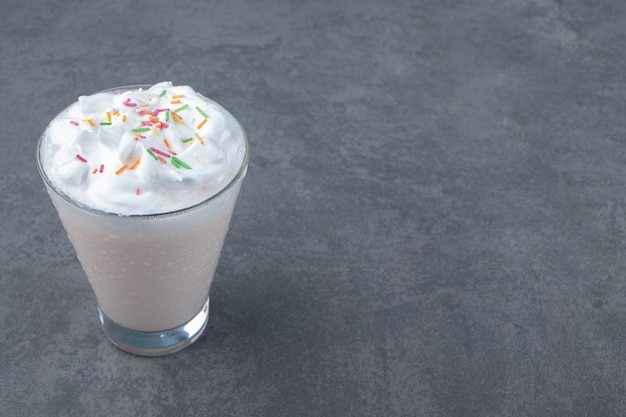 A glass cup of sweet milkshake with whipped cream . high quality photo
