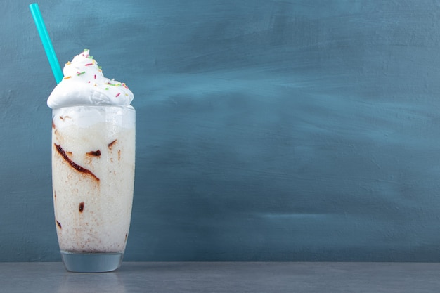 A glass cup of sweet milkshake with whipped cream and sprinkles. high quality photo