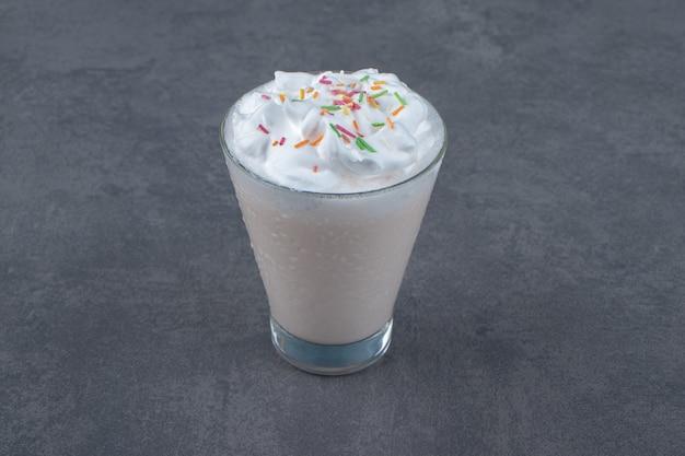 Una tazza di vetro di frullato dolce con panna montata.