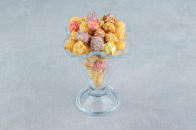 Una tazza di vetro di popcorn multicolori dolci.