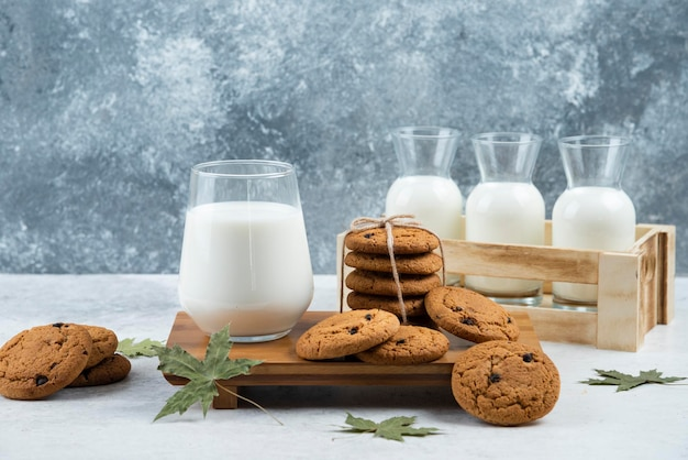 A glass cup of tasty milk with cookies and leaves.