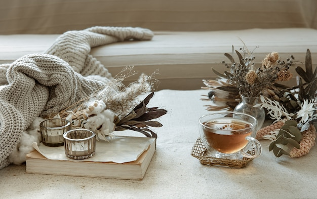 Glass cup of tea, knitted element and dried flowers in the interior of the room.