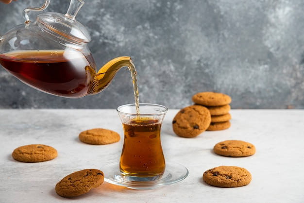 A glass cup of tea with delicious cookies .
