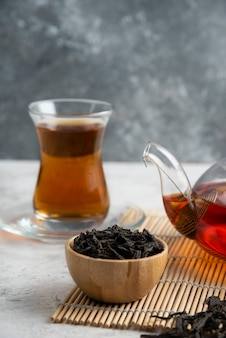 A glass cup of tea with dried loose teas and teapot.