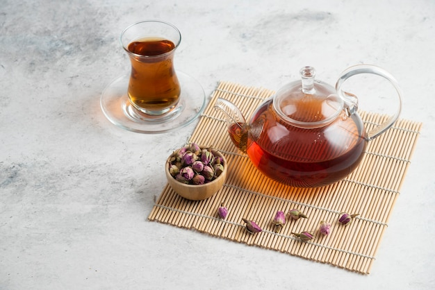 A glass cup of tea with dried roses and teapot
