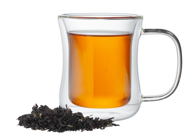 Glass cup of tea with dry tea leaves isolated on white background