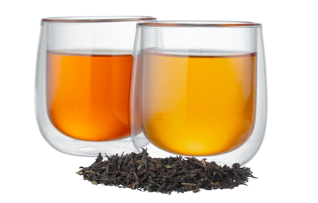 Glass cup of tea with dry tea leaves isolated