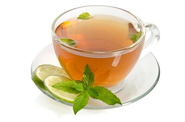 Стеклянная чашка чая с мятой и ломтиками лайма, изолированные на белом