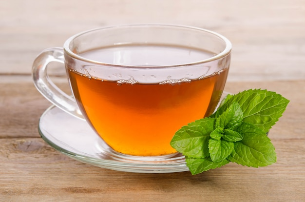 Glass cup of tea with mint leaves on wooden table