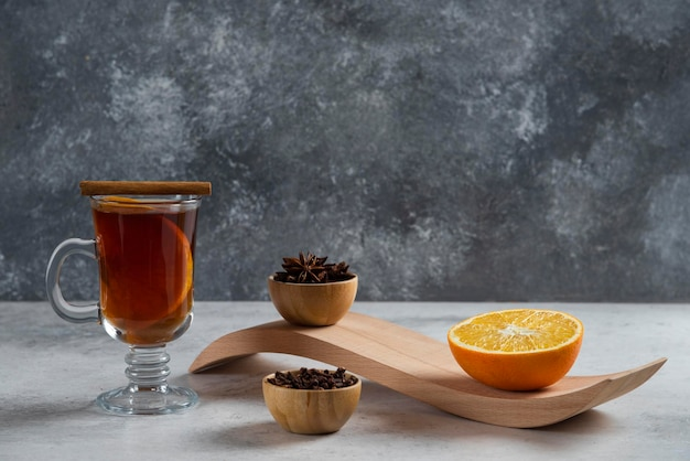 A glass cup of tea with slice of orange and dried loose teas.