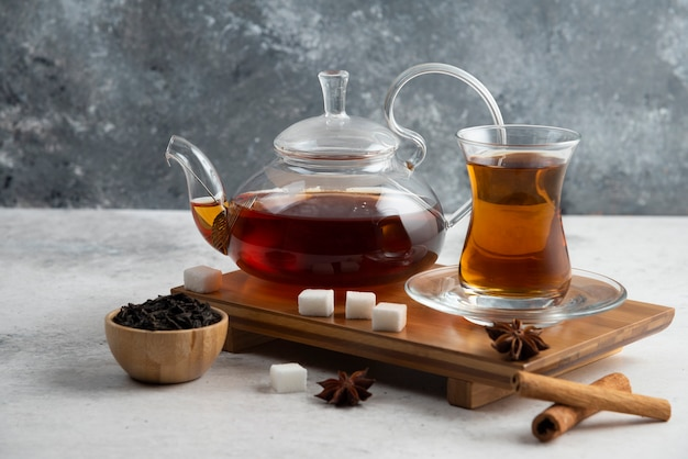 A glass cup of tea with sugar and star anise.
