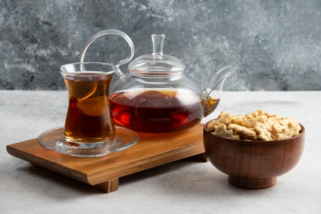 A glass cup of tea with wooden bowl full of crackers.