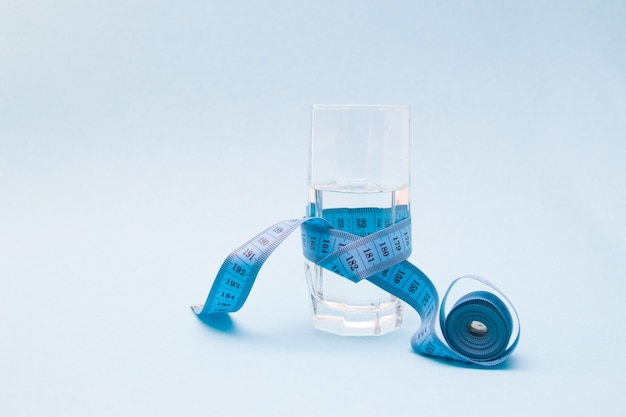 A glass cup of water wrapped in blue measuring tape