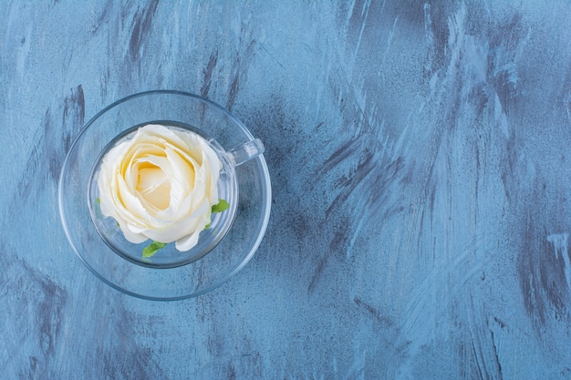 Glass cup of white rose placed on blue.