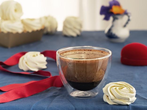 Стеклянная чашка с кофе с молоком на столе, рядом с домашним зефиром. весенние цветы в вазе рядом с зефиром.
