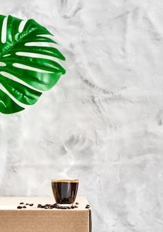 회색 중립 벽에 어두운 향기로운 에스프레소와 유리 컵. 클로즈업, 선택적 초점, 증기 찻잔 위에 상승. 모닝 커피 개념. 볶은 커피 원두가 커피 컵 주위에 배치됩니다.