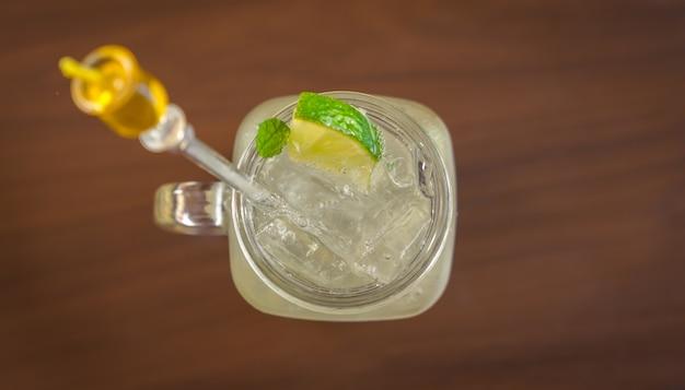 Стеклянная чаша с напитком со льдом и лимоном