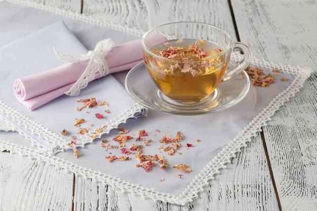 新鮮な緑茶と乾燥したバラのガラスのコップ