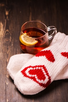 Glass cup with lemon tea and knitted mittens